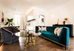mid century living room velvet couch sofa barn farmhouse hardwood floor white brick wall diy gold coffee table green emerald shop-room-ideas Jino Design Ltd eclectic