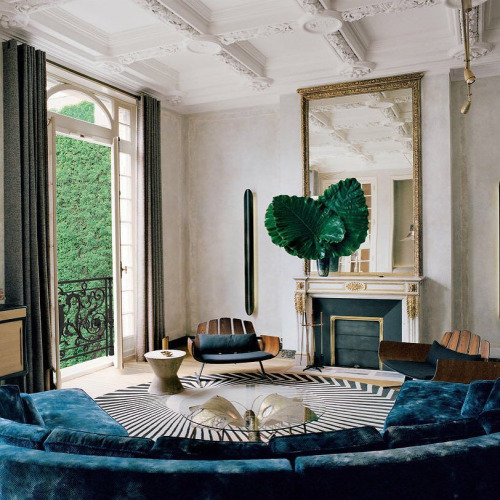 french parisian balcony rod iron black apartment loft round oval couch sofa blue green velvet waffle ceiling detail modern eclectic pinterest zebra abstract rug fireplace mantle