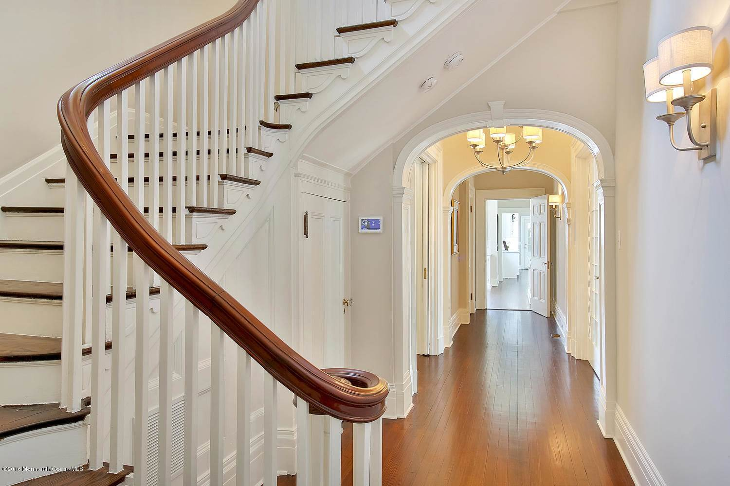 greek colonial georgian mansion architectural style waterfront home luxury mansion million dollar estate gray and white panel siding white and brown staircase arched hallway