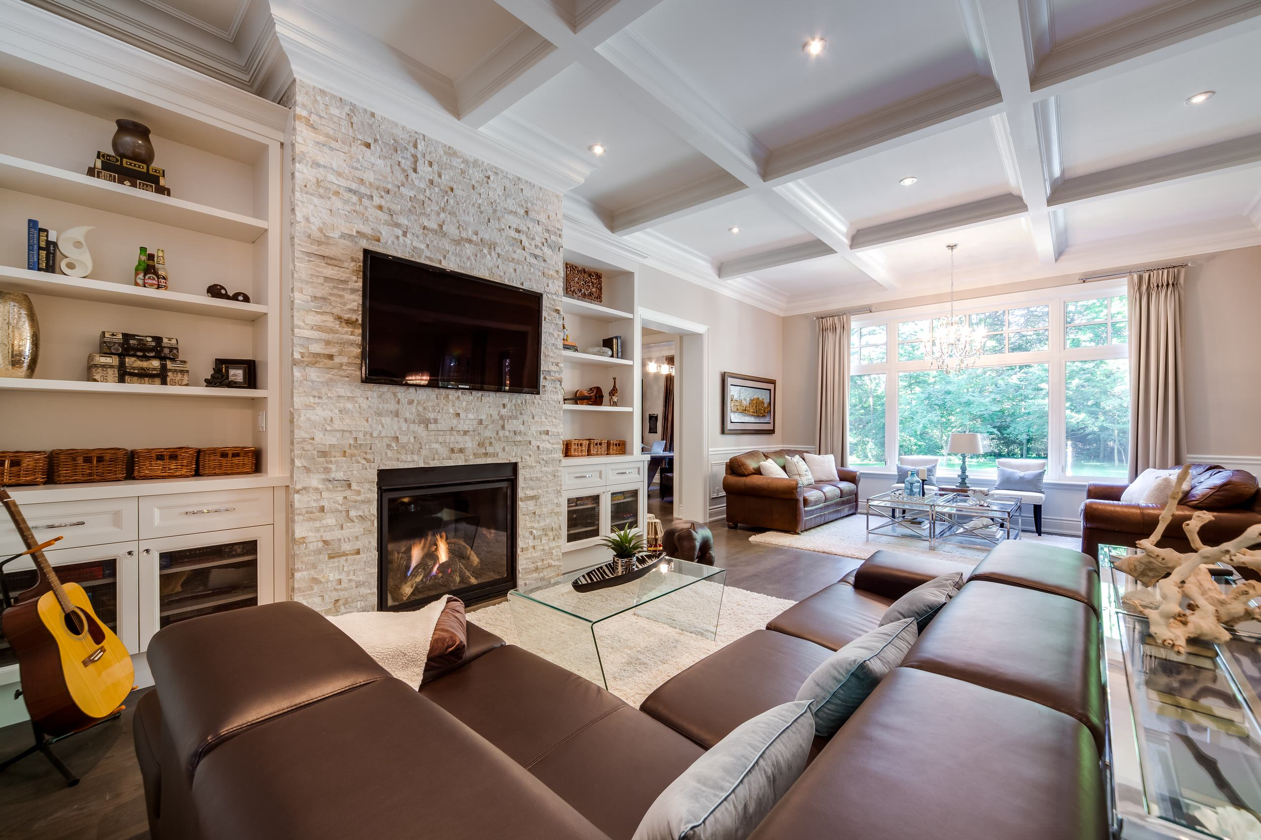 stone tv fireplace ideas cozy country cottage built in bookshelves bookshelf moulding living room waffle ceiling with pot lights leather couches