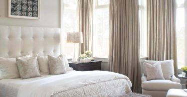 beach-style-bedroom coastal design master bedroom light neutral off white tufted headboard drapes curtains large high windows feminine cozy glam luxury bedroom hotel style